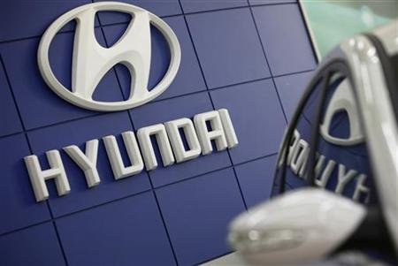 The Hyundai logo is seen next to the company's Sonata sedan at a dealership in Seoul